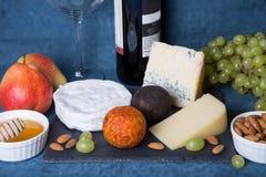 Placa de queso 5 especies de queso, fruta, nueces, botella de vino imágenes de archivo libres de regalías