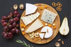 Placa de queso Quesos clasificados con las frutas, las nueces y los pretzeles Comida para el vino imagen de archivo libre de regalías
