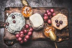 Placa de queso rústica con las diversas salsas de mostaza del queso, de la uva y de la miel, visión superior Imagen de archivo libre de regalías