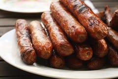 Placa de salsichas barbequed na tabela de madeira Fotografia de Stock
