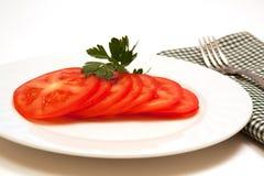 Placa de tomates maduros cortados da videira Fotografia de Stock Royalty Free
