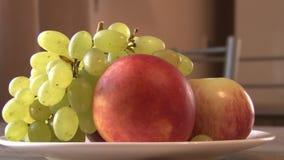 Placa de torneado con la fruta en el fondo blanco, apear, uvas, melocotones, manzana almacen de video