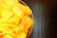 Placa de vidro com as microplaquetas de batata deliciosas friáveis fotos de stock