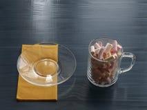 Placa de vidro e marshmallows transparentes no guardanapo e no copo em uma tabela de madeira Foto de Stock