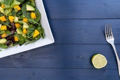 Placa del almuerzo de la ensalada del aguacate del mango en la tabla de madera azul Fotos de archivo libres de regalías