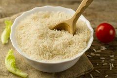 Placa del arroz de grano largo con una cuchara, tomate de cereza, lechuga verde en fondo de madera Imagenes de archivo
