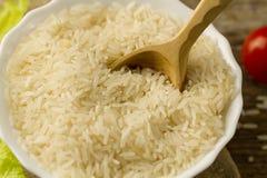 Placa del arroz de grano largo con una cuchara, tomate de cereza, lechuga verde en fondo de madera Imagen de archivo libre de regalías