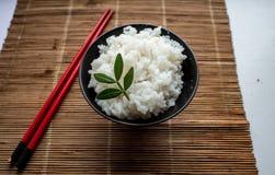 Placa del arroz y de los palillos en una manta de los palillos de bambú foto de archivo