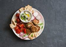 Placa del bocado Albóndigas de la coliflor, tomates, rábano, gluten-libre, galleta y salsa Bocado vegetariano sano Imágenes de archivo libres de regalías