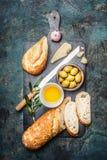 Placa del bocado con las aceitunas, el aceite, el queso y el pan cortado del ciabatta en tabla de cortar rústica oscura Imagen de archivo