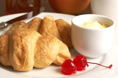 Placa del desayuno con los croissants y las cerezas Imagenes de archivo