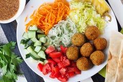 Placa del Falafel en el top a adornar, zanahoria, col, cebolla, pepinos, tomates, aún vida, plato Imágenes de archivo libres de regalías
