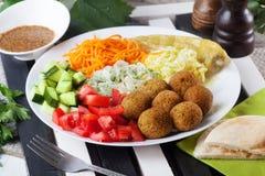 Placa del Falafel en el top a adornar, zanahoria, col, cebolla, pepinos, tomates, aún vida, plato Imagenes de archivo