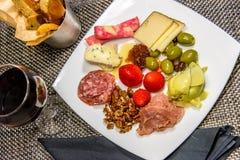 Placa del queso, de la nuez y de la carne con las barras de pan y el vino rojo Imagenes de archivo