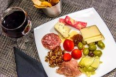 Placa del queso, de la nuez y de la carne con las barras de pan y el vino rojo Imagen de archivo libre de regalías