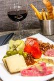 Placa del queso, de la nuez y de la carne con las barras de pan y el vino rojo Fotos de archivo libres de regalías