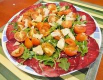 Placa del verano: hojas del cohete, carne secada, parmesano y tomates Fotografía de archivo libre de regalías