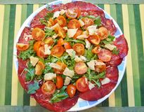 Placa del verano: hojas del cohete, carne secada, parmesano y tomates Imágenes de archivo libres de regalías