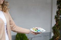 Placa disponible del control de la muchacha con las tortas hechas en casa en la forma del anim Foto de archivo