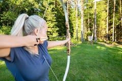 Placa do alvo de Aiming Arrow At do atleta fêmea na floresta Fotos de Stock