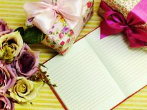 A placa do caderno com caixa de presente e o ramalhete bonito floresce Imagem de Stock Royalty Free