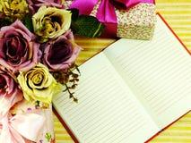 A placa do caderno com caixa de presente e o ramalhete bonito floresce Imagens de Stock