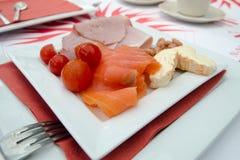 A placa do café da manhã com os tomates dos salmões, do presunto, do queijo e de cereja Imagem de Stock Royalty Free