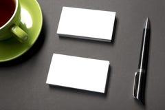 Placa do cartão sobre o copo de café e pena na tabela do escritório Modelo de marcagem com ferro quente dos artigos de papelaria  Imagens de Stock