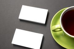 Placa do cartão sobre o copo de café na tabela do escritório Modelo de marcagem com ferro quente dos artigos de papelaria incorpo Fotografia de Stock Royalty Free