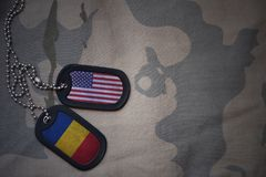 placa do exército, etiqueta de cão com a bandeira de Estados Unidos da América e romania no fundo caqui da textura fotos de stock