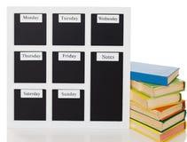 Placa do shedule da semana com a pilha de livros velhos Fotografia de Stock Royalty Free