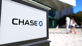 Placa do signage da rua com logotipo de JPMorgan Chase Bank Centro borrado do escritório e fundo de passeio dos povos 3D editoria ilustração do vetor