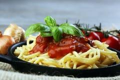 A placa dos espaguetes deliciosos Bolognaise ou Bolonhês com segurelha triturou o molho da carne e de tomate decorado com queijo  Fotografia de Stock Royalty Free