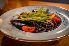 Placa dos espaguetes pretos com tinta do sepia com um molho de marisco fotos de stock