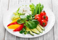 Placa dos legumes frescos com queijo de feta, tomates de cereja, pepino, aipo, pimenta doce e manjericão em uma placa no fundo de Foto de Stock