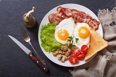 Placa dos ovos fritos, do bacon, dos cogumelos, da salada e do brinde, vista superior imagem de stock royalty free