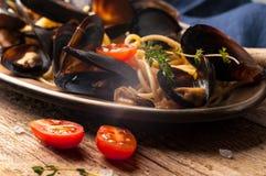 placa dourada do metal com espaguetes deliciosos e os mexilhões italianos tradicionais cozinhados no molho com tomates fotografia de stock