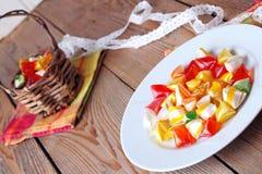 Placa e cesta com os doces doces coloridos Foto de Stock