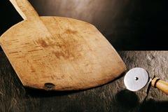 Placa e cortador de madeira de pá da pizza na bancada fotografia de stock