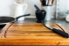 Placa e faca de desbastamento na cozinha cinzenta do tampo da mesa Fotografia de Stock