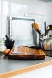 Placa e faca de desbastamento na cozinha cinzenta do tampo da mesa Imagens de Stock Royalty Free