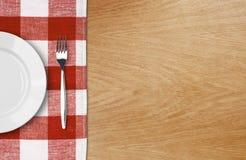 Placa e forquilha brancas na tabela de madeira Fotografia de Stock
