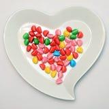Placa en forma de corazón y caramelo coloreado Fotografía de archivo
