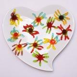 Placa en forma de corazón y caramelo coloreado Imágenes de archivo libres de regalías