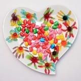 Placa en forma de corazón y caramelo coloreado Imagenes de archivo
