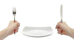 Placa, faca e cutelaria brancas da forquilha nas mãos fotografia de stock royalty free