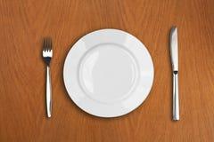 Placa, faca e forquilha brancas redondas na tabela de madeira Fotografia de Stock