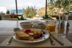 Placa fresca do café da manhã na tabela de madeira que inclui a omeleta, a salsicha, o presunto, o tomate, o pepino, o pão, o suc Imagem de Stock