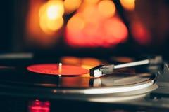 Placa giratoria con el disco de vinilo de LP contra fondo del fuego Fotografía de archivo libre de regalías