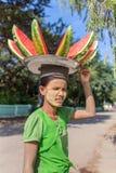 Placa levando da mulher burmese não identificada com a melancia em sua cabeça para a venda em ruas de Bagan, Myanmar Fotos de Stock Royalty Free